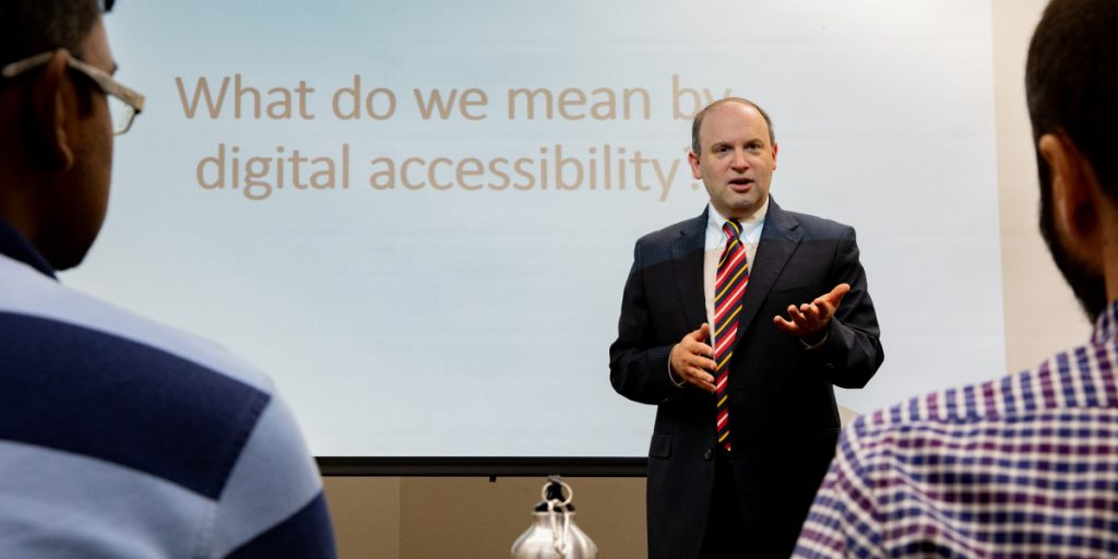 Image of Dr. Jonathan Lazar delivering a lecture on digital accessibility to an audience.