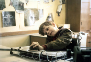 A boy sitting in a wheelchair moves a handpiece across the top of an auto monitoring communication board